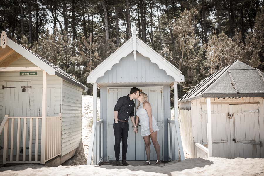 Faded image of a couple standing in front of a blue beach hut at Well-Next-To-See, during their norfolk coast engagement shoot