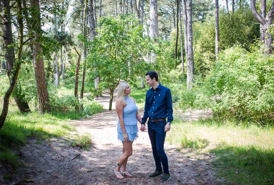 Couple standing on a sandy track in a forrest during their norfolk coast engagement shoot