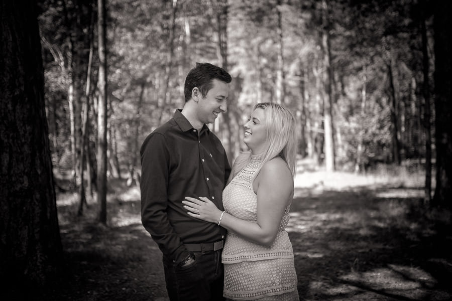 Black and white photograph of couple looking at each other in a forest during their norfolk coast engagement shoot
