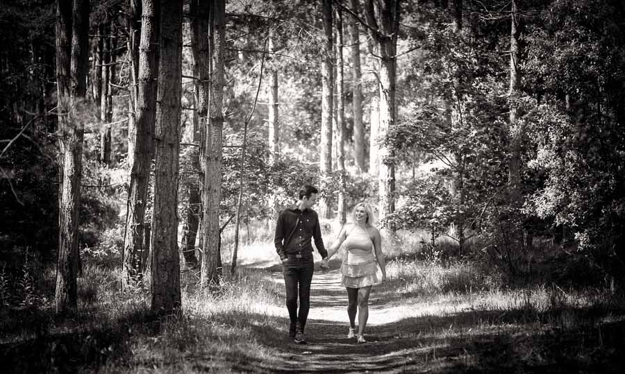 Black and white image of a couple walking hand in hand in a pine forest during their norfolk coast engagement shoot