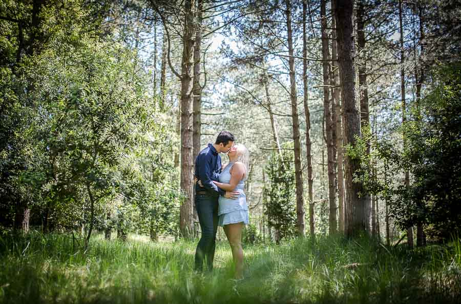 Couple kissing in a pine forest during their norfolk coast engagement shoot
