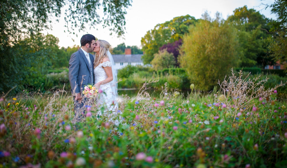 Bride and groom standing in a wild flower meadow at The Granary Barns Wedding.