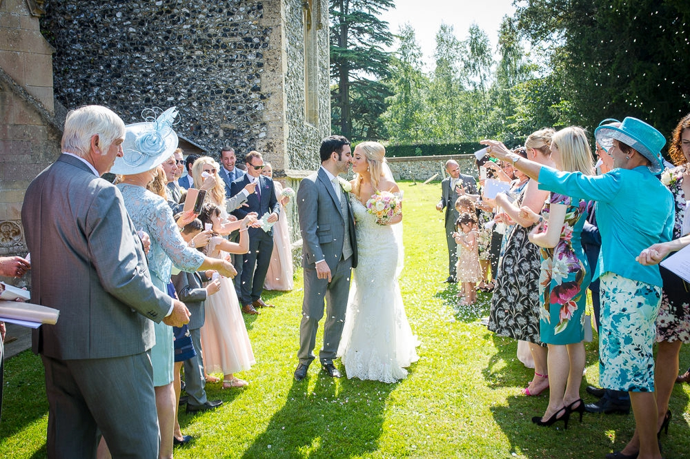 Bride and groom kissing as confetti is thrown during the granary barns wedding