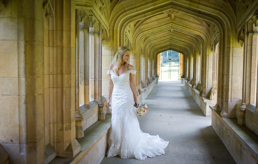 Bride standing in the cloisters at a church before going onto the Granary Barns