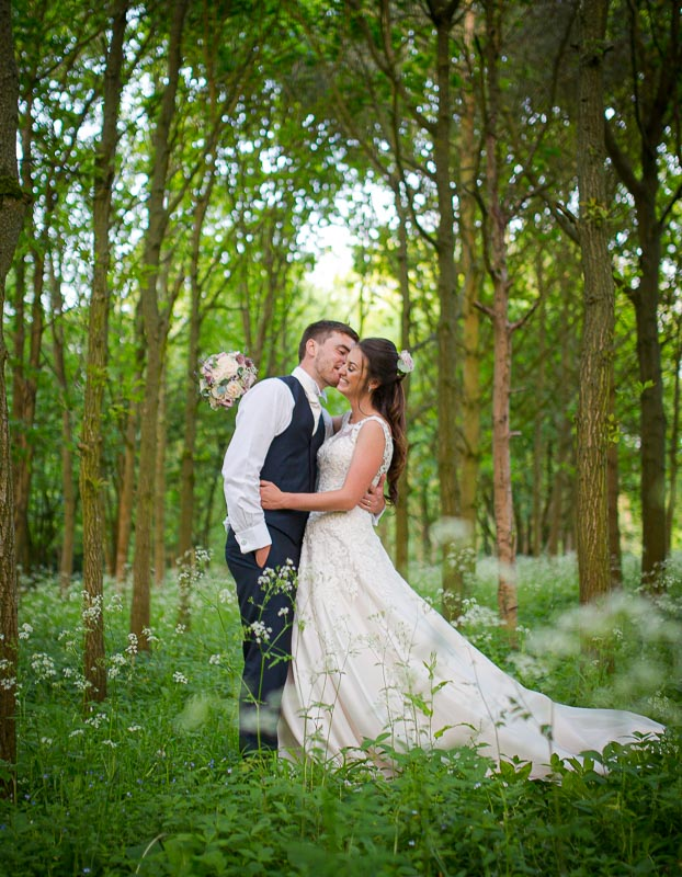 Bride and groom embracing in Longstowe hall wedding, illustrating our wedding photography pricing page.